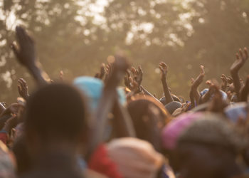 Hands raised in praise in an outdoor worship setting
