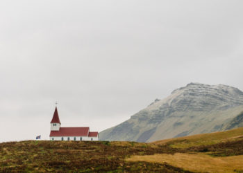 A red roofed church set in a field